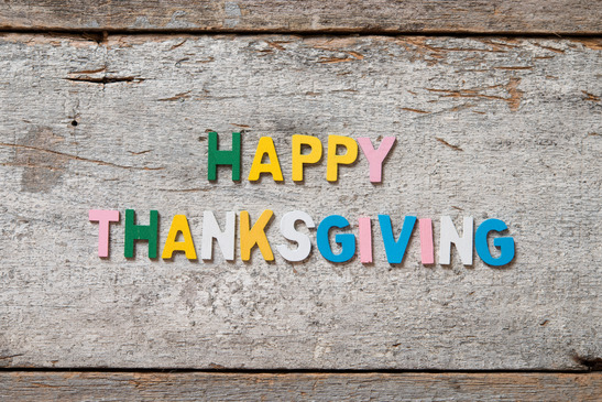 """The colorful words """"HAPPY THANKSGIVING"""" made with wooden letters on old wooden board."""